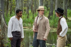 "After being illegally sold into slavery, African-American free man Solomon Northup (Chiwetel Ejiofor, left) finds himself answering to plantation owner Master William Ford (Benedict Cumberbatch, center) and his ruthless overseer, Mr. Tibeats (Paul Dano, right), in ""12 Years a Slave."" Photo courtesy of Fox Searchlight Pictures."