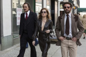"Con artists Irving Rosenfeld (Christian Bale, left) and Sydney Prosser (Amy Adams, center) instruct undercover FBI agent Richie DiMaso (Bradley Cooper, right) on how to conduct a sting in director David O. Russell's excellent new release, ""American Hustle."" Photo by François Duhamel, © Annapurna Productions LLC, courtesy of Columbia Pictures."