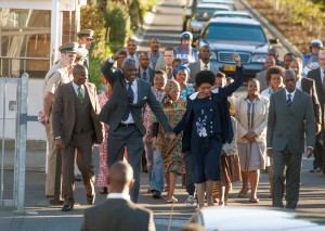 """After a prolonged incarceration, South African human rights activist Nelson Mandela (Idris Elba, center left) is joined by wife Winnie (Naomie Harris, center right) upon his release from prison in """"Mandela: Long Walk to Freedom."""" Photo by Keith Bernstein, courtesy of The Weinstein Co."""
