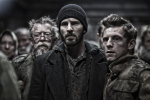 """The rigid class segregation of passengers aboard a post-apocalyptic survival train prompts a revolt of the underprivileged against the power elite, led by insurgent leader Curtis (Chris Evans, center) and his compatriots, Edgar (Jamie Bell, right) and Gilliam (John Hurt, left), in the thrilling new action adventure, """"Snowpiercer."""" Photo courtesy of Radius-TWC."""