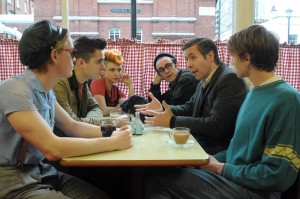"""Miners' representative Dai Donovan (Paddy Considine, second from right) meets with gay community activist Mark Ashton (Ben Schnetzer, second from left) and a contingent of London's gay and lesbian community (Freddie Fox, left; Faye Marsay, third from left; Joseph Gilgun, third from right; George MacKay, right) who support the nation's striking coal miners in director Matthew Warchus's inspiring new comedy, """"Pride."""" Photo by Nicole Dove, courtesy of CBS Films."""