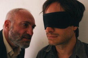 "Iranian-born journalist Maziar Bahari (Gael García Bernal, right) is subjected to the intense interrogation of a ""specialist"" (Kim Bodnia, left) seeking to coerce an espionage confession out of him in writer-director Jon Stewart's debut feature, ""Rosewater."" Photo by Nasser Kalaji, courtesy of Open Road Films."