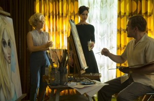 """On a rare visit to the artist's studio, painter Margaret Keane (Amy Adams, left) gives her friend Dee-Ann (Krysten Ritter, center) a glimpse into the alleged creative genius of her husband, Walter (Christoph Waltz, right), in """"Big Eyes."""" Photo courtesy of The Weinstein Co."""