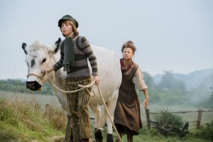 """A poor farm woman (Tracey Ullman, right) instructs her son, Jack (Daniel Huttlestone), to sell their aging cow to raise money to pay bills, but realizing this goal depends on how well the young lad follows his mother's instructions in """"Into the Woods."""" Photo by Peter Mountain, courtesy of Disney Enterprises, Inc."""