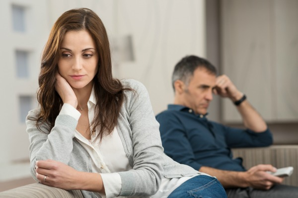 bigstock-Sad-Couple-Sitting-On-Couch-Af-61279874