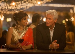 """Mystery guest Guy Chambers (Richard Gere, right) checks in to the Marigold Hotel under the watchful eye of Mrs. Kapoor (Lillete Dubey, left), mother of the operation's owner, in the delightful comedy sequel, """"The Second Best Exotic Marigold Hotel."""" Photo courtesy of Fox Searchlight Pictures."""