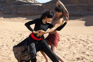 """Iranian-born dancer Afshin Ghaffarian (Reece Ritchie, right) and his performing partner, Elaheh (Freida Pinto, left), stage a secret recital for a select audience in the desert when doing so in public was otherwise impossible in the new fact-based biopic, """"Desert Dancer."""" Photo courtesy of Desert Dancer Production LTD."""