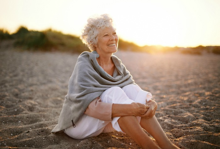 bigstock-Cheerful-Old-Woman-Sitting-On--63367348