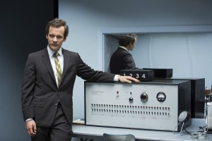 """Yale University researcher Stanley Milgram (Peter Sarsgaard) poses with the equipment from his famous obedience experiment conducted in 1961 as re-created in the engaging new biopic, """"Experimenter."""" Photo courtesy of Magnolia Pictures."""