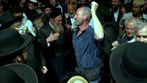 """Filmmaker Steven E. Bram (center) dances with orthodox Jewish men while on a pilgrimage to Israel, as depicted in the director's documentary, """"Kabbalah Me."""" Photo courtesy of First Run Features."""