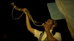 """A man blows a ceremonial horn known as a shofar, as seen in the documentary, """"Kabbalah Me."""" Photo courtesy of First Run Features."""