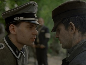 """Saul Ausländer (Géza Röhrig, right), a prisoner assigned to a special work detail at the infamous Auschwitz concentration camp, frequently runs afoul of German authorities, such as Oberscharführer Busch (Christian Harting, left), in the gripping new release from Hungary, """"Son of Saul."""" Photo courtesy of Sony Pictures Classics."""