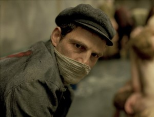 """Saul Ausländer (Géza Röhrig), a prisoner assigned to a special work detail at the infamous Auschwitz concentration camp, routinely engages in gruesome tasks like scrubbing the floor of the facility's gas chamber in the visceral new release, """"Son of Saul."""" Photo courtesy of Sony Pictures Classics."""