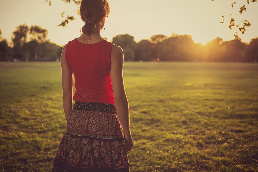 A young woman is standing in a park and is admiring the sunset