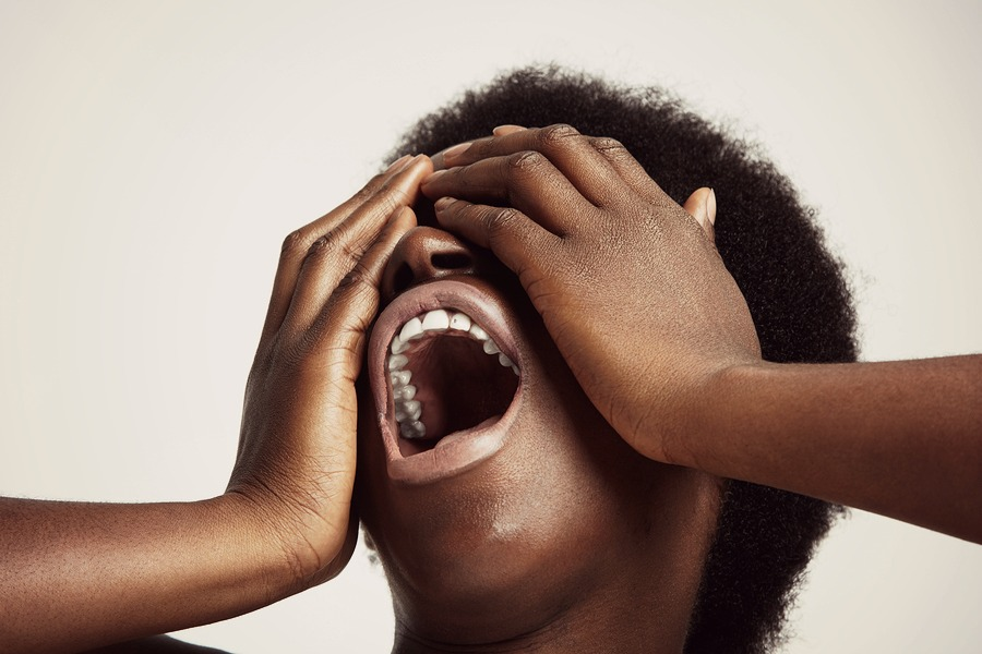 screaming black woman closed eyes with her arms
